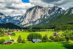 Campi verdi sbalorditivi e villaggio alpino con le montagne, Altaussee, Austria Immagini Stock