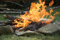 Camping. Campfire in the morning. Huge flames. Stones in front of fire stock photo