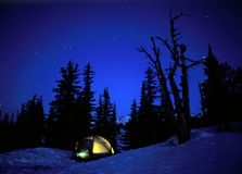 Camping. In a glowing tent under the stars in winter royalty free stock image