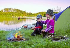 Camping. Children in tents on the shore of the lake Royalty Free Stock Images