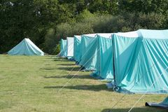 Camping. A row of blue tents on a green field with trees in the background Royalty Free Stock Images