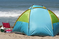 Camping. Blue tent and pink beach chair at a beach campsite Stock Image