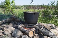 Camping, adventure, cooking a meal over an open flame campfire. Summer hike; Tourist kettle over the fire royalty free stock photo