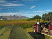 Camping adventure in Iceland - tent and old off-road car with op. En door - view on colorful mountains meadow and trees with blue sky Stock Photos