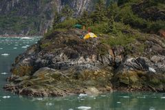 Camping adventure on the rock in the fjord in Alaska. Stock Images