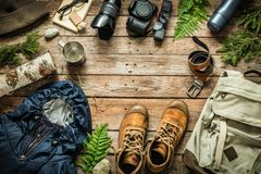 Camping or adventure trip scenery concept flat lay. Camping or adventure trip scenery concept. Backpack, jacket, boots, belt, thermos and camera on wooden stock photo