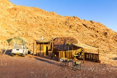 Camping in Africa with wooden shelter cabin in desert sunrise stock photography