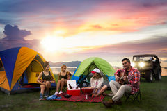 Camping of asian man and women group. Camping of asian men and women group, relaxing, sing a song and cooking, with ligh from car and tent Royalty Free Stock Images