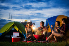 Camping of asian man and women group. Camping of asian men and women group, relaxing, sing a song and cooking, with ligh from car and tent Stock Photo