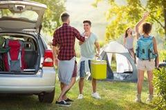 Camping-Ausflug, junge glückliche Menschen sagen angekommene Freunde Guten Tag Stockfotos