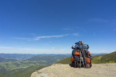 Camping with backpacks in the mountains against the blue sky. Stock Photos
