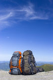 Camping with backpacks in the mountains against the blue sky. Royalty Free Stock Photo