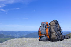 Camping with backpacks in the mountains against the blue sky. Royalty Free Stock Images