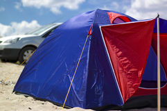 Camping on the beach. Blue and red tent on the beach with cloudy sky in background stock images