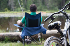 Camping bliss. A teenage boy fishing by the lakeside in his camp chair. Focus on the bike Stock Images