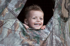 Camping Boy. Excited Happy Young toddler boy peeking through a camouflage camping tent Royalty Free Stock Photo