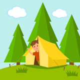 Camping. Boy traveler looks out of the tent in the middle of a forest. The concept of of summer holiday outdoors Royalty Free Stock Images
