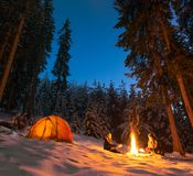 Camping with campfire and tent outdoors in winter stock photography