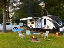 Camping on the campground with travel trailer Royalty Free Stock Photo