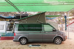Camping car on the campground. Camping car with a convertible roof under a shadow net on a campground Royalty Free Stock Photos