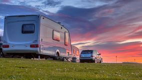 Camping caravans and cars sunset crop. Camping caravans and cars parked on a grassy campground under beautiful sunset stock photo