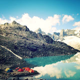 Camping cerca del efecto alpino del vintage del lago Tiendas coloridas Montañas del Cáucaso fotos de archivo