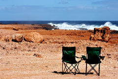 Camping chairs. Crashing waves and 2 camping chairs stock photo