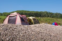 Camping containing two tents and located on pebble shore. Stock Photography