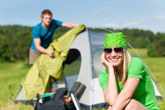 Camping couple build-up tent sunny countryside. Young camping couple build-up tent in summer meadows countryside stock photography