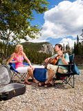 Camping Couple with Guitar. A happy couple with a guitar outdoors having fun royalty free stock photos