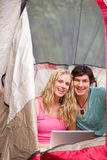 Camping Couple with Laptop. A portrait of a happy camping couple with a laptop, smiling at the camera royalty free stock image