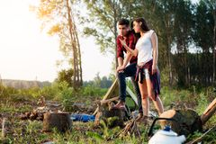 Camping couple looking at view in forest. Campers smiling happy outdoors in forest. Camping young couple looking at view in forest. Campers smiling happy royalty free stock image