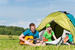 Camping couple playing guitar by tent countryside Royalty Free Stock Photography