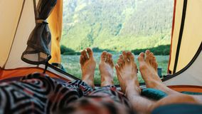 Camping couple shows close-up of feet from tent on rocky mountains background. stock video footage
