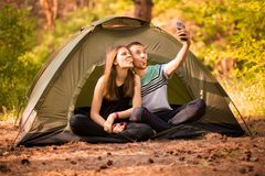 Camping couple in tent taking selfie. Happy friends having fun togheter. Concept people. Lifestyle and technology stock image