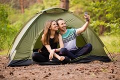 Camping couple in tent taking selfie. Happy friends having fun togheter. Concept lifestyle and technology. Camping couple in tent taking selfie. Happy friends royalty free stock photos