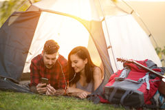 Camping couple in tent taking selfie using smartphone. Camping hipster couple in tent taking selfie using smartphone royalty free stock photo