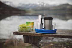 Camping cuisine. Picnic food on wooden table by the lake. Royalty Free Stock Photo