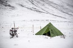 Camping. Cyclist camping in the snow mountain stock image