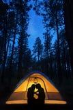 Camping de couples de silhouette sous des étoiles dans la tente Photographie stock libre de droits