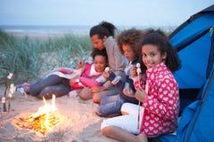 Camping de famille sur la plage et les guimauves de grillage Image libre de droits