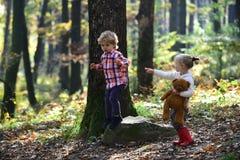 Camping de garçon et de fille en bois Le garçon et la fille jouent des jeux dans la forêt d'automne Photos libres de droits