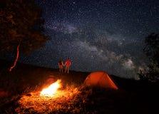 Camping de nuit avec un feu de camp sous un ciel étoilé lumineux avec la manière laiteuse lumineuse Photos stock