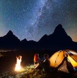 Camping de nuit La paire avec du charme de se reposer de touristes face à face dans la tente avant près du feu de camp brille des Images libres de droits