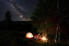Camping de nuit Les amis par le feu de camp se reposant sur des rondins parmi des arbres s'approchent de la tente sous le ciel ét Photo stock