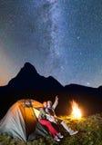 Camping de nuit Paires de randonneurs s'asseyant près de la tente et du feu de camp et appréciant le ciel étoilé incroyablement b Images stock