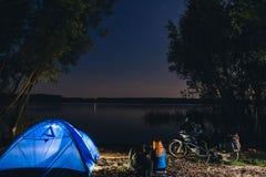 Camping de nuit sur le rivage de lac L'homme et la femme s'assied Couplez les touristes appr?ciant en stup?fiant la vue du ciel n photos stock