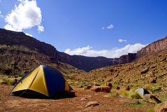 Camping in desert. A view of a colorful tent set up in the desert near a high mesa or butte Stock Photography