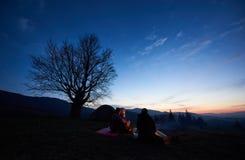 Camping en montagnes à l'aube Groupe de trois touristes s'asseyant devant la tente Photos libres de droits