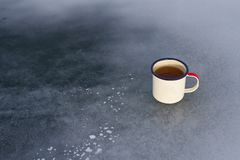Camping enameled metal traveler`s mug with herbal tea with copy space on the ice of Lake Baikal on a sunny day. Camping enameled metal traveler`s mug with Stock Photo